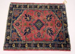 A SMALL PERSIAN RUG. mid 20th Century, red ground with stylized decoration. 3ft 3ins x 2ft 8ins.