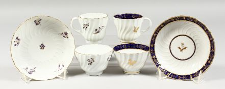 TWO BARR WORCESTER TRIOS, one painted with puce flower, the other with a blue and gilt border,