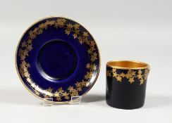 AN EARLY 20TH CENTURY CROWN DEVON BLUE AND GILT COFFEE CAN AND SAUCER.