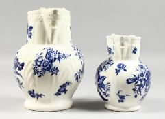 A GRADUATED PAIR OF DECORATIVE ENGLISH PORCELAIN MASK JUGS printed with fir cones and roses in