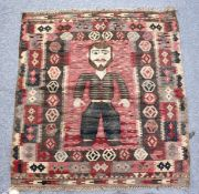 AN UNUSUAL SMALL FLATWEAVE KELIM RUG, the central panel depicting a standing male figure. 3ft 4ins x