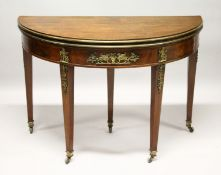 A FRENCH EMPIRE MAHOGANY DEMILUNE FOLD-OVER CARD TABLE, with ormolu mounts, on tapering square
