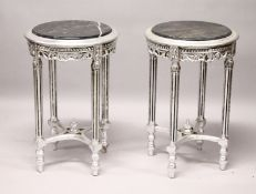 A PAIR OF ROUND SILVERED WOOD TABLES with marble tops.