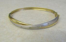 9ct gold bangle, two tone effect with cubic zirconia accents total weight 6.4 g