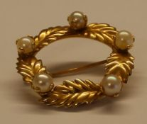 Small circular brooch with leaf & pearl detail marked 14k, width approximately 2.5cm, weight 3.0g
