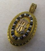 Tested as 14 ct gold ornate monogrammed locket with seed pearls and tigers eye stones total weight