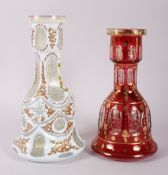 "A 20th century Bohemian ruby glass mallet-shaped vase with gilt decoration, 10"" high, and a"