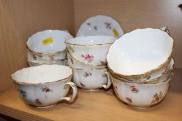 A quantity of early 20th century Meissen teacups, saucers and a sugar bowl (one cracked)