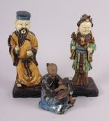 "Two Chinese figures, on stands, largest 9 1/2"" high, and another figure of a seated man, 5"" high ("