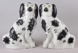 A pair of late 19th century Staffordshire models, seated spaniels, with black sponged decoration,