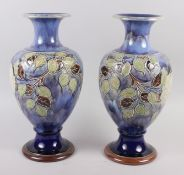 A pair of Royal Doulton blue glazed vases with flared tops and ovoid bodies, tub lined decoration of