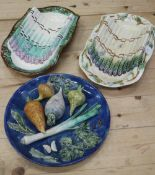 "Two Continental pottery asparagus servers, 15"" long, and a Palissy style dish with vegetable"