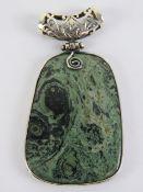 A large green hardstone pendant having h