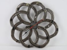 A wall clock formed from eight horseshoes and having central quartz movement, slightly a/f,