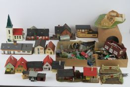 A quantity of Triang Hornby model railway trackside buildings together with cars, signs, fencing,