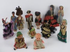 A quantity of assorted vintage dolls in traditional dress including three sleepy eyed dolls.