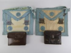 Masonic; Two leather regalia pouches each containing a lambskin apron, marked respectively for Bro.