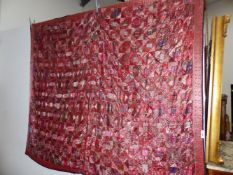 AN INDIAN PATCHWORK PANEL WORKED WITH RED SILK GEOMETRIC SHAPES WITHIN A FLORAL BORDER AND BACKED BY