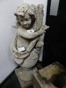 A VINTAGE WEATHERED GARDEN FIGURE OF PUTTI WITH WHEATSHEAF ATOP A SPHERE ON A PLINTH BASE. H.