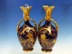 A PAIR OF REDON LIMOGES BLUE GROUND VASES WITH GILT HANDLES AND FOLIAGE DECORATION. H 24cms.