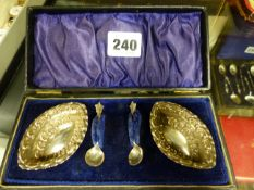 A CASED PAIR OF SILVER SALTS WITH SPOONS.