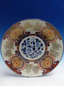 A JAPANESE FUKUGAWA IMARI DISH, THE RUYI FRAMED FLORAL LAPPETS ALTERNATING WITH STANDS OF BAMBOO AND