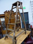 A SLINGSBY PINE LADDER SLOPING TO A RIGHT ANGLE SUPPORT WITH IRON WHEELS AT THE BASE SPRUNG SO