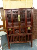 A CHINESE HARDWOOD FOOD CUPBOARD, THE PIERCED SCROLLING FOLIAGE PANELS AT THE TOP OVER SLATTED DOORS