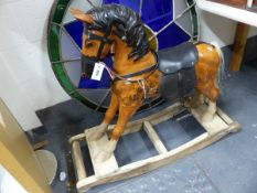 A CARVED AND PAINTED CHILD'S ROCKING HORSE WITH LEATHER SADDLE AND REINS. W.106cms.