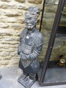 A CHINESE BLACKENED TERRACOTTA SOLDIER STANDING WITH HIS HANDS CLASPED ON HIS LACQUER ARMOURED