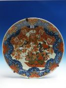 AN ANTIQUE JAPANESE IMARI DISH, THE CENTRAL VASE OF FLOWERS BELOW TASSELLED KNOTS WITHIN A BLUE