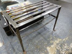 A STEEL TWO TIER TRIVET, THE RECTANGULAR TOP FORMED OF SIX STRAPS, THE FRONT LEGS WITH PAD FEET. W