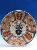 A JAPANESE IMARI DISH WITH THE CENTRAL VASE OF FLOWERS ENCLOSED BY ALTERNATING RIM LAPPETS. Dia.