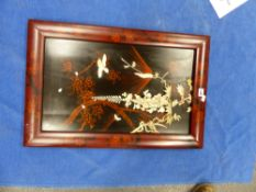 A JAPANESE RED FRAMED BLACK LACQUER PANEL INLAID WITH A BIRD AND BUTTERFLY BY FLOWERING WISTERIA