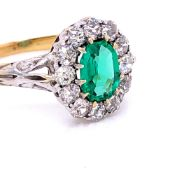 AN EMERALD AND DIAMOND CLUSTER RING. THE PRINCIPLE MIXED CUT EMERALD IN A TWELVE CLAW SETTING