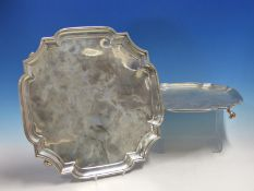 AN EARLY 20th C. HALLMARKED SILVER TRAY OF SHAPED SQUARE FORM ON FOUR SCROLL SUPPORTS TOGETHER