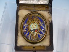 AN ANTIQUE HAND PAINTED MINIATURE OF A SAINT WITHIN GILDED FOLDED PAPER RIZA CONTAINED IN A BRASS