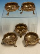 A SET OF FIVE VICTORIAN HALLMARKED SILVER REPOUSSE DECORATED TABLE SALTS ON HOOF FEET TOGETHER