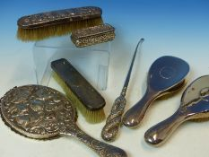 A HALLMARKED SILVER THREE PIECE DRESSING TABLE SET, A FURTHER REPOUSSE DECORATED MIRROR AND BRUSH, A