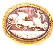 AN OVAL CAMEO BROOCH OF CHARIOT AND DRIVER PULLED BY THREE HORSES IN FULL GALLOP, SET IN A PIERCED