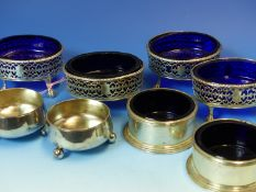 A SET OF FOUR 19th C. PIERCED HALLMARKED SILVER TABLE SALTS WITH BLUE GLASS LINERS, A FURTHER PAIR