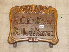 A DANISH WOOD CARVERS SIGN FRAMED IN ART NOUVEAU FLOURISHES ABOUT K C ERIKSEN BILLEDSKAERER. H 30