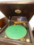 AN OAK CASED CLIFTOPHONE WIND UP GRAMOPHONE, THE GREEN BAIZE TOPPED TURNTABLE ABOVE DOORS OPENING TO