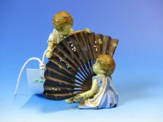 AN AUSTRIAN BRONZE GROUP OF A GIRL SEATED WITH A BLACK FAN WHILE A BOY HOLDS THE TOP, LATER