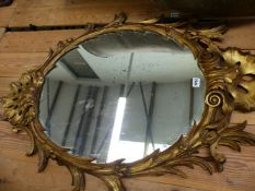 A CARVED GILTWOOD OVAL WALL MIRROR IN THE GEORGIAN TASTE.