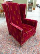 AN EDWARDIAN WING BACK ARMCHAIR WITH PERIOD VELOUR UPHOLSTERY ON SHORT SQUARE TAPERED LEGS AND