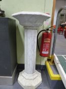 A CARVED WHITE MARBLE PEDESTAL BIRD BATH ON FLUTED COLUMN. H.108cms.