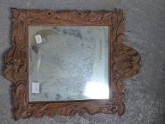 A RECTANGULAR MIRROR WITHIN A PINE FRAME CARVED WITH FOLIAGE, A MASK AT ITS BASE. 42.5 x 34.5cms.