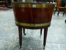 AN ANTIQUE BRASS BOUND MAHOGANY OVAL WINE COOLER ON STAND. BRASS CASTERS AND HANDLES. H. 67 x W.