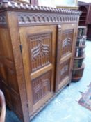 A HAND MADE GOTHIC REVIVAL CARVED OAK SIDE CABINET WITH LINEN FOLD SIDE PANELS AND CARVED WITH
